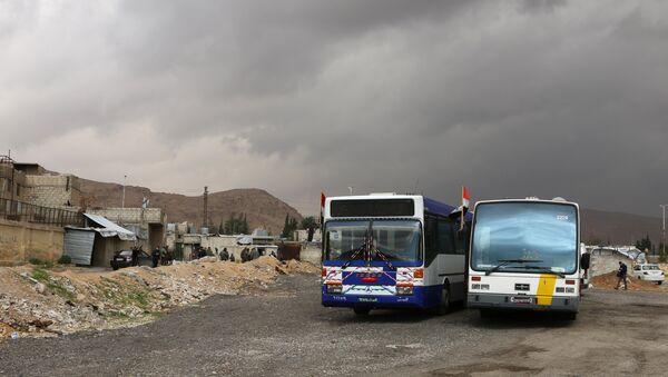 Pripadnici sirijskih vladinih snaga stoje pored autobusa na kontrolnom punktu u predgrađu Damaska tokom operacije izvlačenja skoro 400.000 stanovnika Istočne Gute da napuste ovu enklavu - Sputnik Srbija