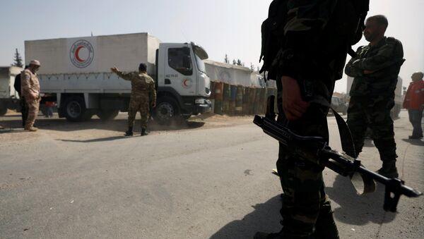 Sirijski vojnici pored kamiona sirijskog Crvenog polumeseca koji nose pomoć u predgrađu Damaska - Sputnik Srbija