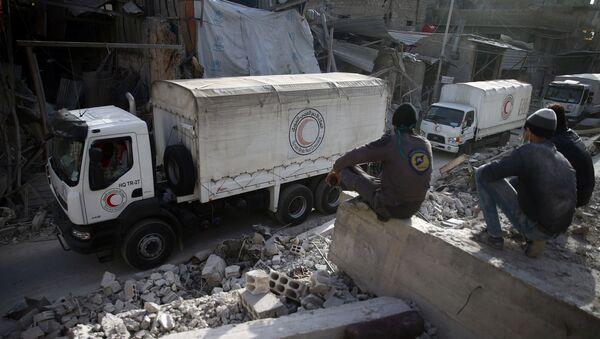 Припадници цивилне заштите посматрају пролазак конвоја хуманитарне помоћи сиријског арапског Црвеног полумесеца кроз опкољени град Дума у Источној Гути - Sputnik Србија