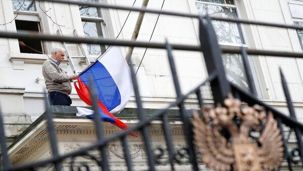 Čovek skida zastavu Rusije sa zgrade ruske diplomatske misije u Londonu - Sputnik Srbija