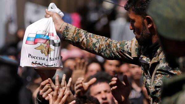 Pripadnici sirijske vojske dele humanitarnu pomoć ruskih snaga civilima koji su napustili Istočnu Gutu - Sputnik Srbija