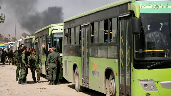 Pripadnici sirijske vojske stoje pored autobusa kojima se pripadnici terorista i članovi njihovih porodica evakuišu iz Haraste - Sputnik Srbija