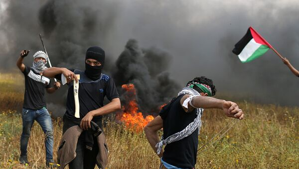 Палестински демонстратор држи секиру током сукоба са израелским трупама у граду Гази 30. марта 2018. - Sputnik Србија