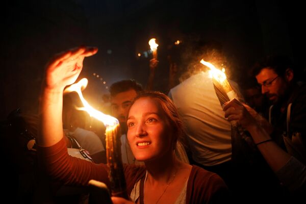 Верници у Храму васкрсења Христовог у Јерусалиму током паљења Благодатног огња - Sputnik Србија