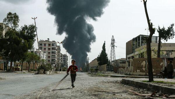 Dečak trči ulicom ispred oblaka dima nakon vazdušnog napada na Dumu u Istočnoj Guti - Sputnik Srbija