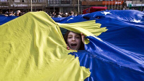 Албанка у Приштини вири испд заставе тзв. Косова - Sputnik Србија