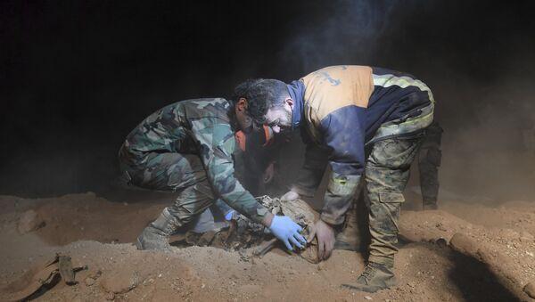Чланови Сиријских снага безбедности уклоњају посмртне остатке у откривеним масовним гробницама за које се верује да садрже тела цивила убијених од стране исламских милитаната, у селу Вави близу града Раке у Сирији. - Sputnik Србија