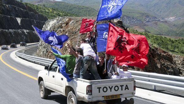 Људи машу заставама Албаније и НАТО-а у Албанији. - Sputnik Србија