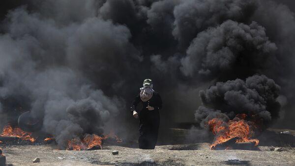 Žena iz Palestine isprd crnog dimom iz gorućih guma tokom protesta u Gazi, ponedeljak, 14. maja 2018. - Sputnik Srbija