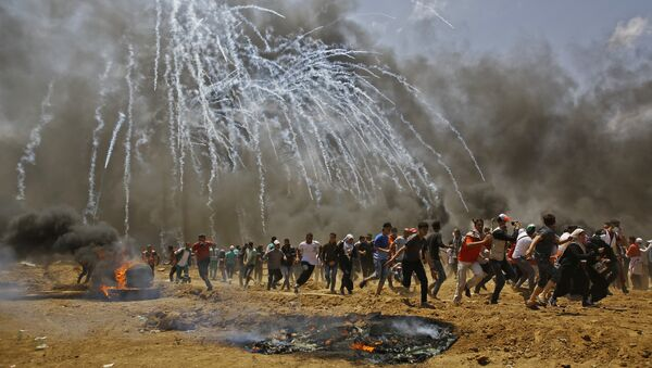 Палестинци трче да се сакрију од сузавца током сукоба са израелским снагама безбедности на граници Израела и Појаса Газе - Sputnik Србија