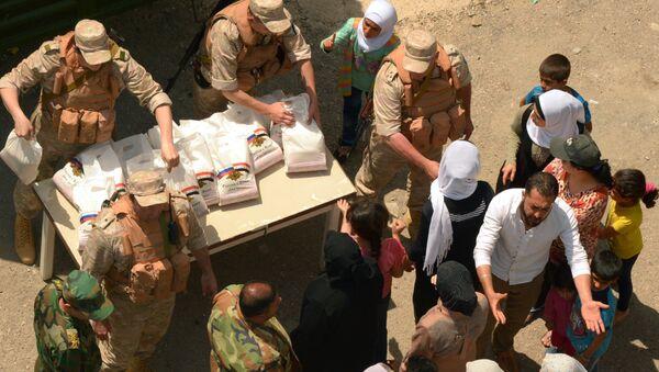 Oficiri Centra za pomirenje zaraćenih strana u Siriji dele rusku humanitarnu pomoć u izbegličkom kampu Ras el Basit u sirijskoj provinciji Latakija - Sputnik Srbija