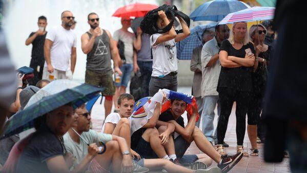 Београђани и поред кише прате утакмицу Србија - Костарика на мундијалском трг. - Sputnik Србија