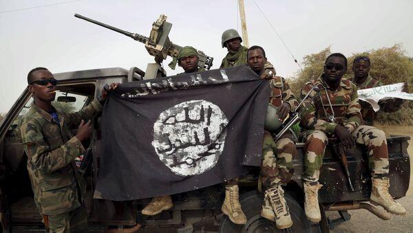 Nigerijski vojnici drže zastavu Boko Harama koju su zaplenili u nedavno obnovljenom gradu Damasaku, Nigerija, 18. marta 2015. - Sputnik Srbija