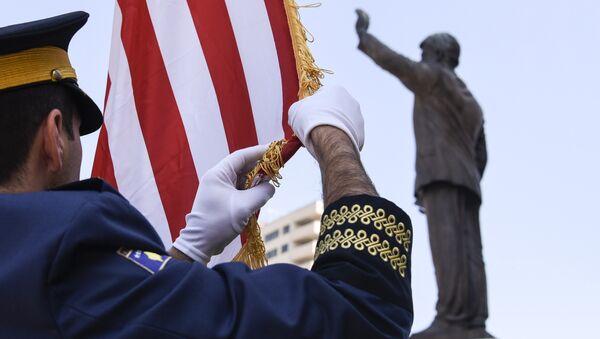 Vojnik tzv. Kosova podiže zastavu SAD pored spomenika Bilu Klintonu u Prištini - Sputnik Srbija