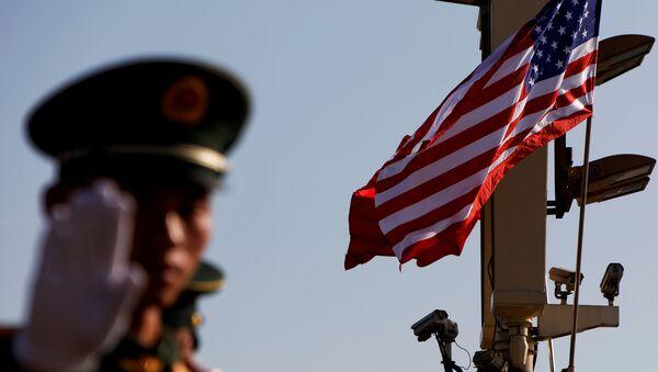 Kineski policajac stoji ispod kamera za nadzor i zastava SAD i Kine u blizini Zabranjenog grada u Pekingu - Sputnik Srbija