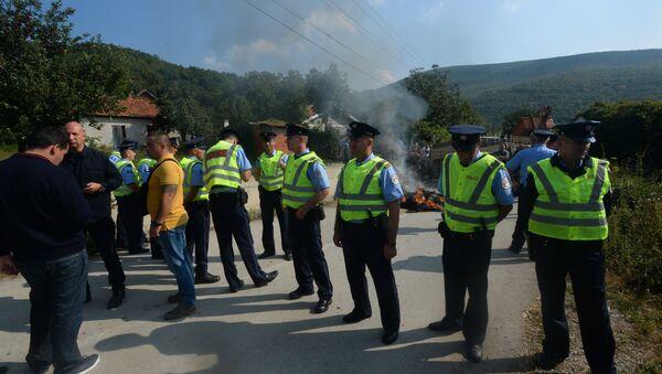 Pripadnici policije stoje pored blokade koju su napravili Albanci na putu ka selu Banje na Kosovu i Metohiji - Sputnik Srbija