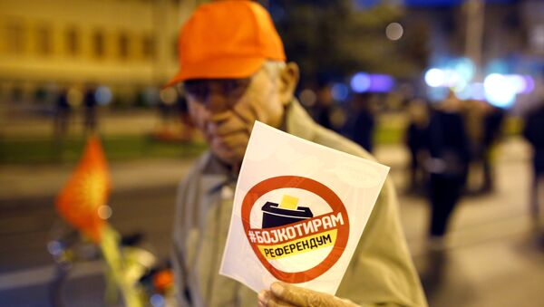 Čovek sa flajerom koji poziva na bojkot referenduma u Makedoniji. - Sputnik Srbija