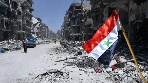 Zastava Sirije u oslobođenom logoru palestinskih izbeglica na jugu Damaska - Sputnik Srbija