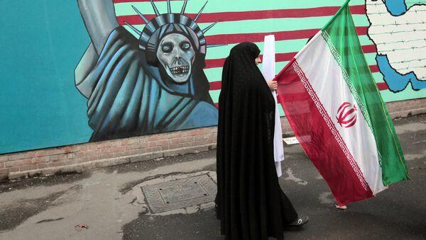 Иранка носи националну заставу док пролази поред мурала на којем је приказана америчка Статуа слободе - Sputnik Србија