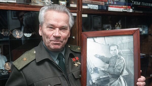 Čuveni ruski konstruktor vatrenog oružja i izumitelj čuvenog automata AK-47, Mihail Kalašnjikov, sa svojom fotografijom iz vremena kada je konstruisao svoj automat. - Sputnik Srbija