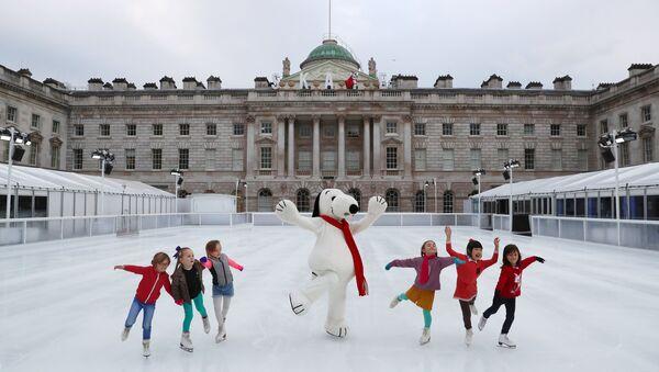 Деца клизају са маскотом Снупија испред Сомерсет хауса у Лондону. - Sputnik Србија