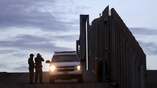 Pripadnici američke granične patrole stoje pored ograde na granici koja odvaja Tihuanu u Meksiku od San Dijega u SAD - Sputnik Srbija