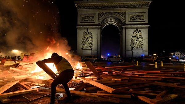 Припадник покрета жути прслуци додаје дрва на ватру испред Тријумфалне капије у Паризу 24. новембра 2018. - Sputnik Србија