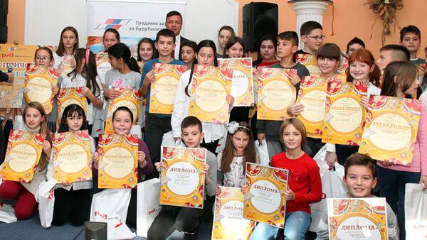 Zamenik generelanog direktora RŽD ineternešnala Masurbek Sultanov sa decom kojoj su uručene diplome - Sputnik Srbija