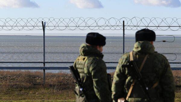 Руски граничари поред ограде подигнуте на Криму на граници са Украјином - Sputnik Србија