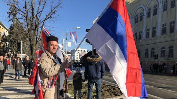 Čovek sa zastavama na ulici Banjaluke očekuje defile - Sputnik Srbija