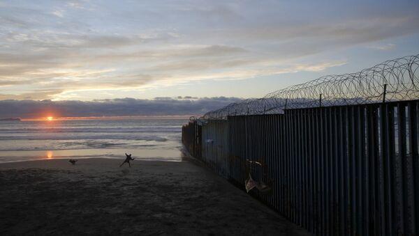 Човек се игра са псом поред зида на граници САД и Мексика - Sputnik Србија