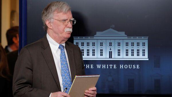 Саветник америчког председника за националну безбедност Џон Болтон држи у руци белешке на брифингу у Белој кући - Sputnik Србија
