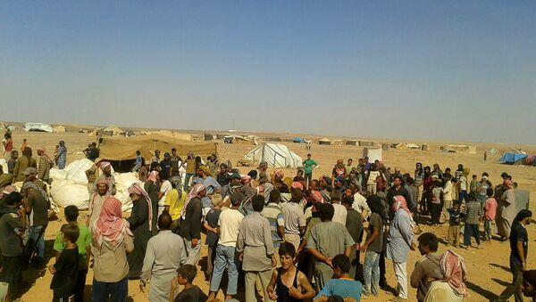 Људи се окупљају да преузму основне намирнице и другу помоћ у избегличком кампу Рукбан на граници Јордана и Сирије - Sputnik Србија