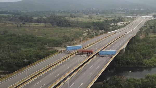 Cisterna, prikolica kamiona i privremena ograda blokiraju međunarodni most Tjenditas u blizini Kukute u Venecueli, u pokušaju da se zaustavi humanitarna pomoć iz Kolumbije - Sputnik Srbija