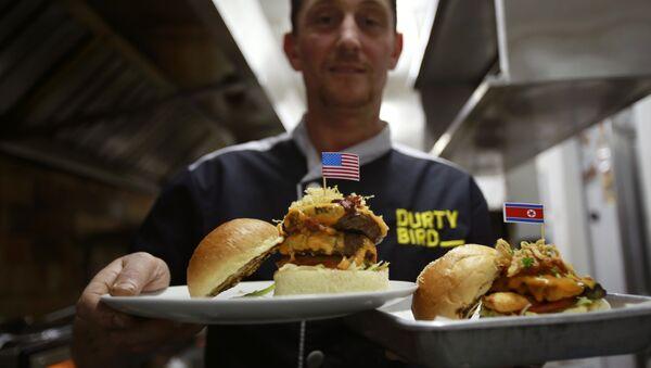 Menadžer restorana pokazuje hamburgere Prljavi Donald i Kim Džong Njam - jela inspirisana samitom američkog i severnokorejskog lidera, Donalda Trampa i Kim Džong Una, u Vijetnamu - Sputnik Srbija