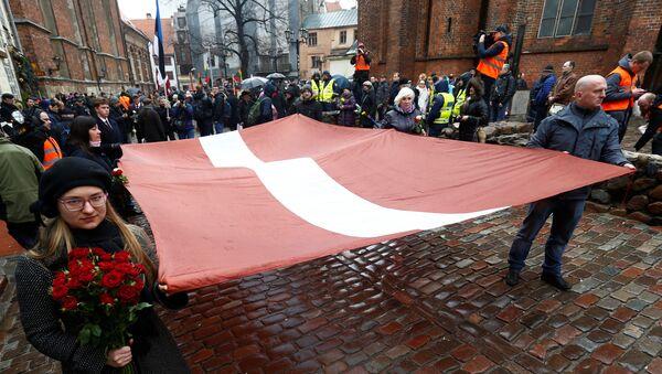 Људи носе заставу на обележавању летонске нацистичке легије Вафен СС у Риги - Sputnik Србија