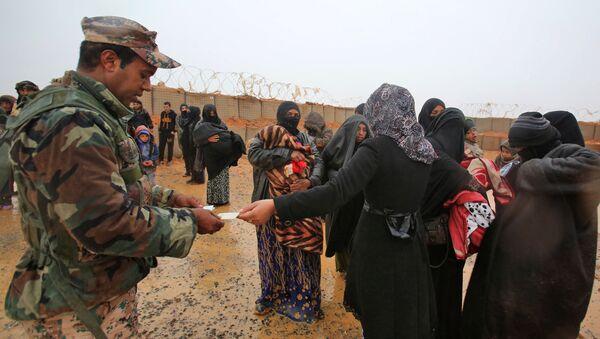 Jordanski vojnik proverava identifikacione kartice sirijskih izbeglica u kampu Rukban - Sputnik Srbija