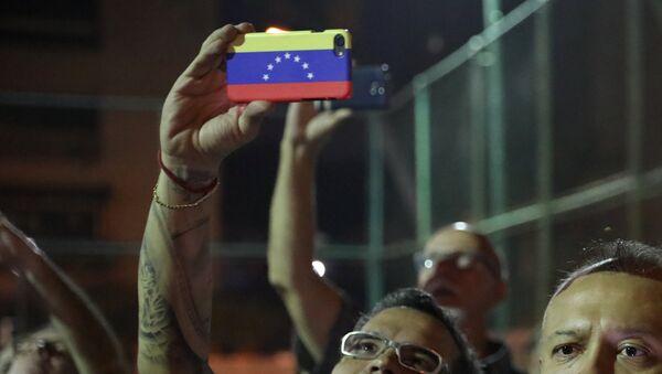 Човек држи мобилни телефон у бојама заставе Венецуеле - Sputnik Србија