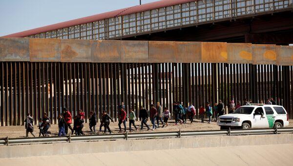 Амерички граничници спроводе мигранте на граници са Мексиком који су покушали нелегално да пређу границу са Сједињеним Америчким Државама - Sputnik Србија