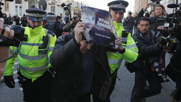 Policija hapsi demonstranta ispred ispred Kraljevskog suda u Londonu koji protestuje zbog hapšenja osnivača Vikiliksa Džulijana Asanža - Sputnik Srbija
