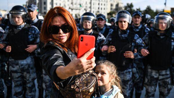 Žena sa detetom se fotografiše ispred kordona policije na neodobrenom protestu u Moskvi - Sputnik Srbija