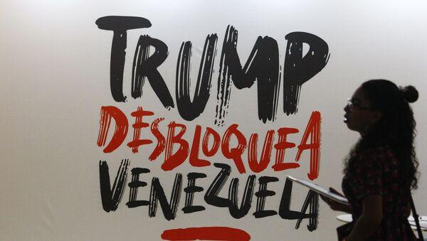 Žena prolazi pored transparenta na kojem na španskom piše Trampe, deblokiraj Venecuelu u Karakasu - Sputnik Srbija
