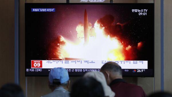 Људи гледају извештај о лансирању ракета у Северној Кореји на железничкој станици у Сеулу - Sputnik Србија