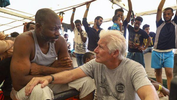 Ричард Гир међу мигрантима на броду. - Sputnik Србија