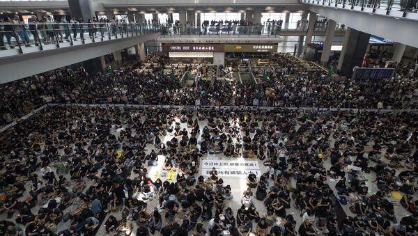Demonstranti sede u sali aerodroma na protestu u Hongkongu - Sputnik Srbija