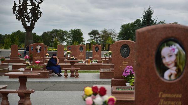 Жена плаче на гробљу Град анђела у Беслану где су сахрањени погинули у терористичком нападу 1. септембра 2004. године. - Sputnik Србија