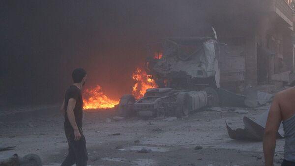 Људи пролазе поред пожара и рушевина након ваздушног напада на сиријску провинцију Идлиб - Sputnik Србија