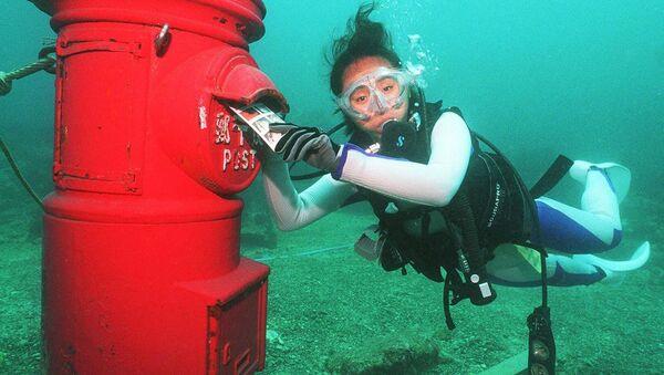 Жена ронилац ставља пластифицирано писмо у поштанско сандуче постављено на дубини од 10 метара на дну мора крај обале Сусамија, префектура ВакаЈама, 7. јула 1999. године. - Sputnik Србија