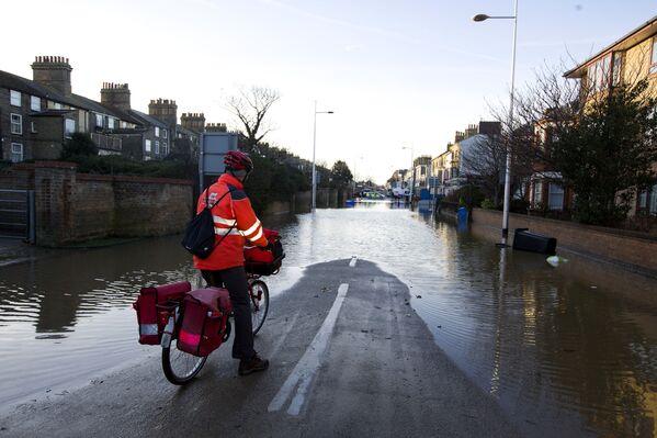 Поштар се зауставља и гледа поплављену улицу у Ловестофту, на истоку Енглеске, 6. децембра 2013. године, након што је плимни налет погодио локације дуж источне обале Британије.  - Sputnik Србија