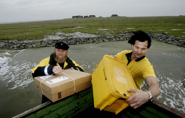 Немачки скипер са најдаљег севера Фиде Нисен и његов колега Андреас Оберауер, за кога се каже да је најсевернији њемачки поштар, доносе пакете и писма становницима малог острва Гроеде у Северном мору у уторак, 5. децембра 2006. - Sputnik Србија